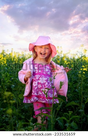 Little girl in pink hat on the field - stock photo