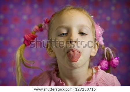 Little girl in pink making faces on a purple background - stock photo