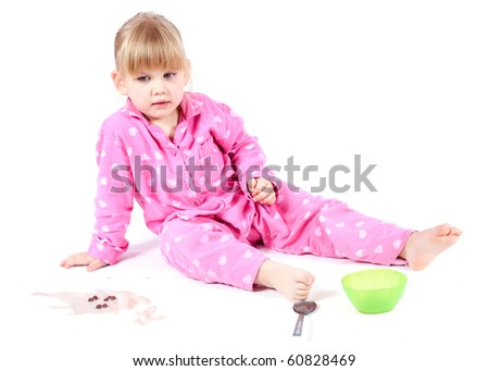 little girl in pink pajamas eating cereal with milk