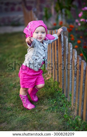 Little girl in pink shoes near the fence.