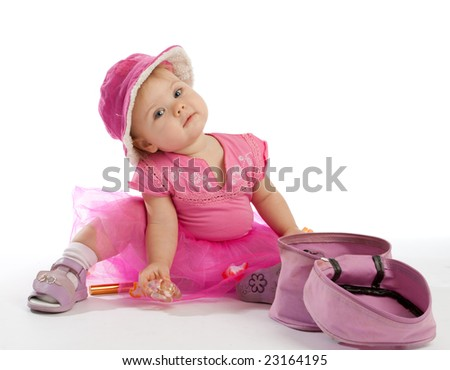 Little girl in pink sitting beside cosmetics box - stock photo