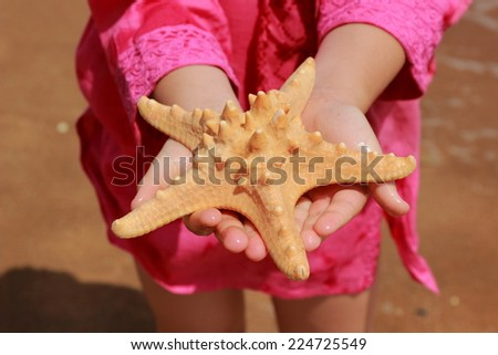 Little girl in pink summer dress holding huge star fish over sand background of Black Sea, East Crimea, Russia - stock photo