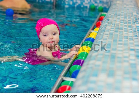 little girl in pink swimsuit in the pool - stock photo