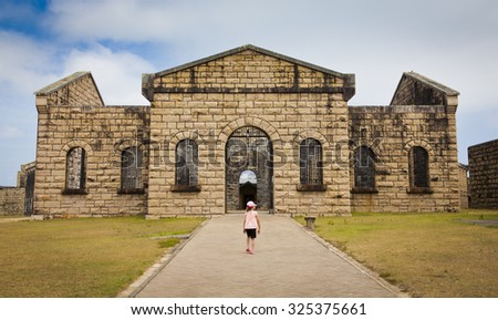 Little girl in pink walks towards Trail Bay Gaol, New South Wales. - stock photo