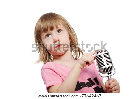 Little girl in pink with microphone holds her forefinger on the top of microphone. - stock photo