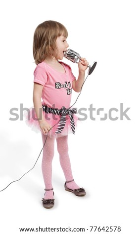 Little girl in pink with microphone stands in full-length half-turned and sings. - stock photo