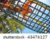 Little girl in playground, high abowe walking over on net. - stock photo