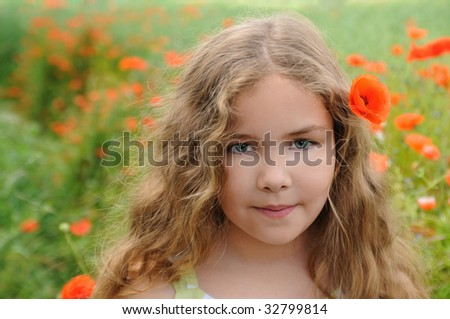 Little girl in poppy meadow with flower in her hair - stock photo