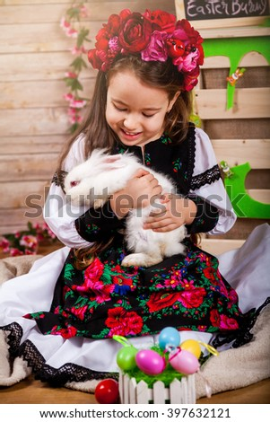 Little girl in popular Romanian costume enjoying the Easter holidays and playing with a rabbit  - stock photo