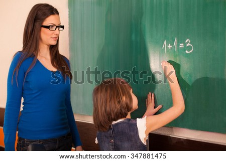 Little girl in primary school writing mathematics task on chalkboard while teacher looking at her