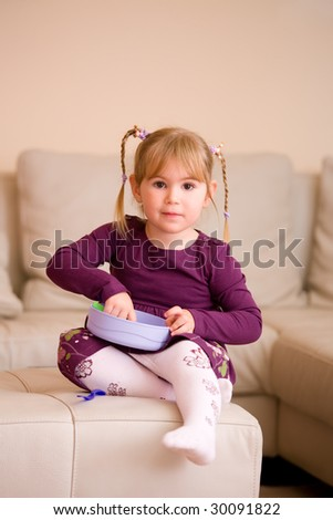 Little girl in purples dress, playing with plastic toy dishes, sitting on couch at home.