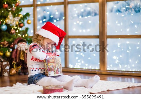 Little girl in red christmas hat with gift box - stock photo