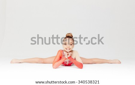 Little girl in red dress doing gymnastic split. Isolated on white background. - stock photo