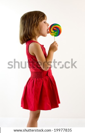 Little girl in red dress licking a lollipop - stock photo