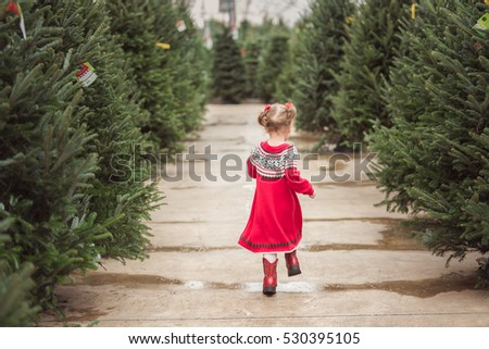 Little girl in red dress on the Christmas tree farm.