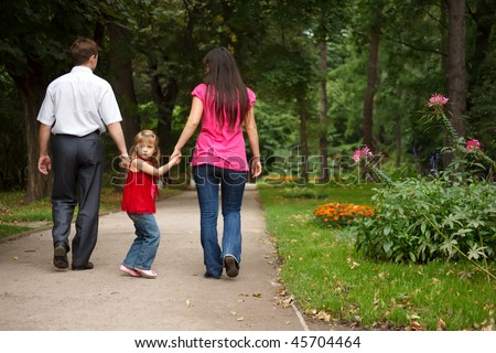 Little girl in red dress together with parents walks in summer garden. Girl holds parents for hands. - stock photo