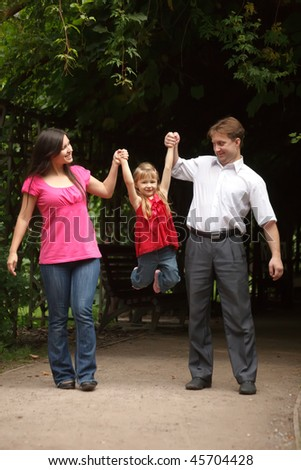 Little girl in red dress with father and mother in park. Girl plays being shaken on hands of parents. - stock photo