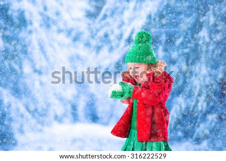 Little girl in red jacket and green knitted hat catching snowflakes in winter park on Christmas eve. Kids play outdoor in snowy winter forest. Children catch snow flakes on Xmas. Toddler kid playing. - stock photo