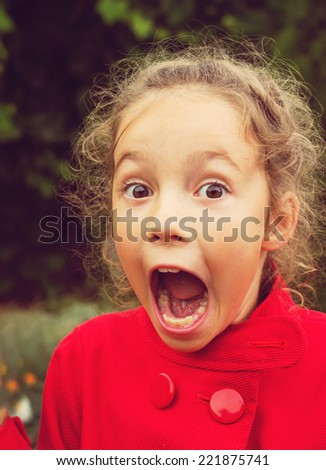 Little girl in red jacket is shocked and surprised and so happy about it.  - stock photo