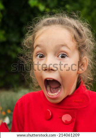 Little girl in red jacket is surprised and so happy about it. - stock photo