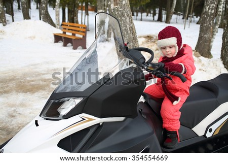 Little girl in red overalls sitting behind the wheel of a snowmobile in forest - stock photo