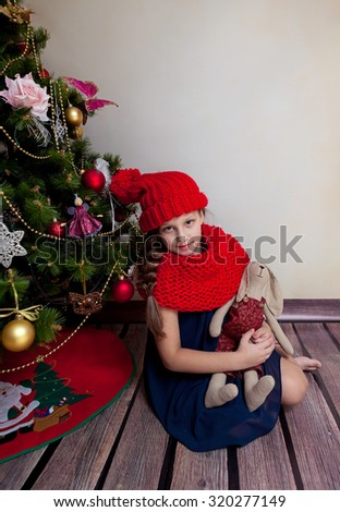 Little girl in red scarf and hat sitting by Chrismas tree - stock photo