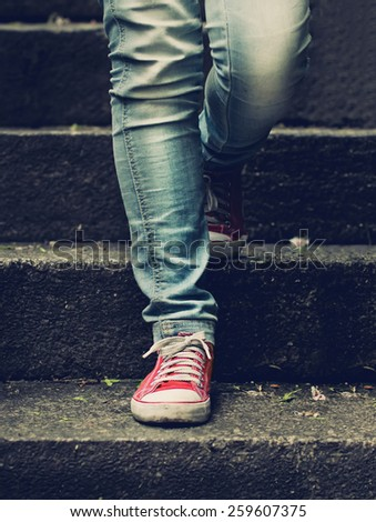 Little girl in red sneakers and jeans making first step on the stairs - stock photo
