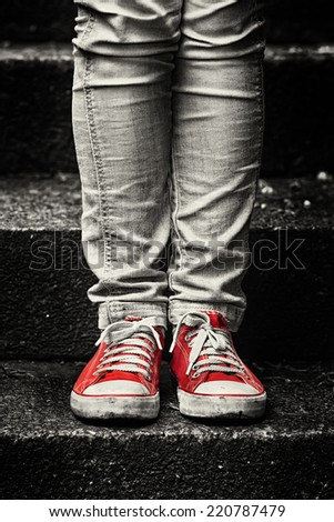 Little girl in red sneakers and jeans standing on the stairs. Making first step. - stock photo