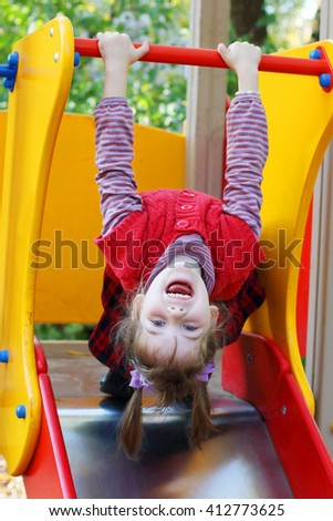 Little girl in red vest hung on hand head down on playground