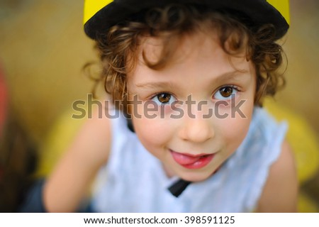 Little girl in roller skates in park at summer. Pretty child, kid riding a roller. Close-up portrait of cheerful preschool girl wearing roller skates and protective equipment. - stock photo