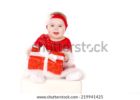 little girl in Santa costume. A baby sitting in a Santa suit with gift box in hands on white background. Studio shot - stock photo