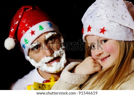 Little girl in santa hat and santa claus in background