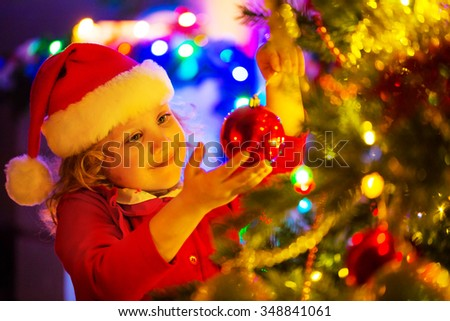 Little girl in Santa hat decorates a Christmas tree - stock photo