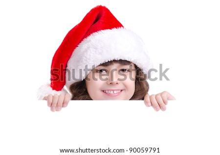 Little girl in Santa hat hiding behind the blank board