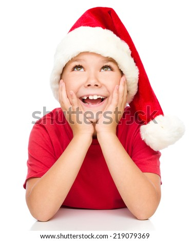 Little girl in santa hat is daydreaming supporting her head with hands, isolated over white - stock photo