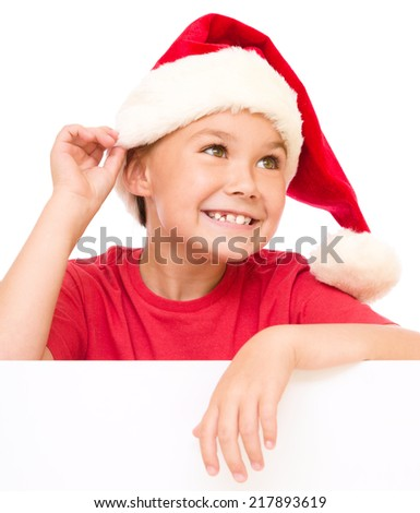 Little girl in santa hat is holding blank board and showing ear like listening, isolated over white - stock photo