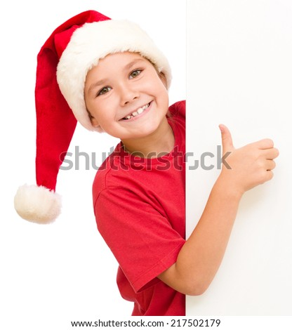 Little girl in santa hat is holding blank board and showing thumb up sign, isolated over white - stock photo