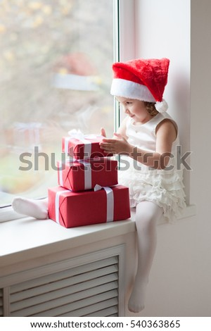 little girl in Santa hat sitting at the window with gifts