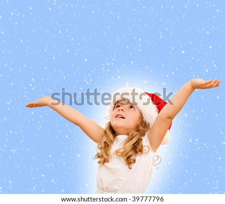 Little girl in santa hat waiting for christmas, looking up among falling snowflakes - isolated