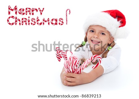 Little girl in santa hat with lots of candy canes - happy holidays - stock photo