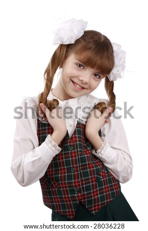 Little girl in school uniform. Pupil is trifling with hair. Isolated on white in studio. - stock photo