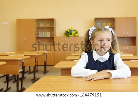 Little girl in school uniform sits at school desk and looks away in classroom in first grade for her alone. - stock photo
