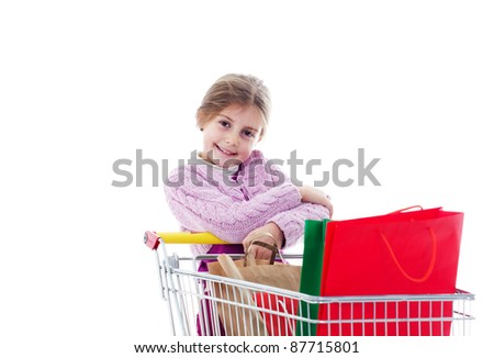 Little girl in shopping with shopping cart and colored bags