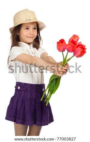 Little girl in straw stretching forward red tulips