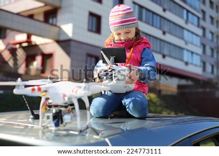 Little girl in striped hat sitting on top of car with radio control in her hands and quadcopter - stock photo