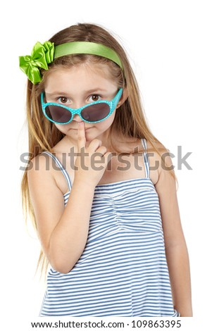 Little girl in striped sundress and green band in hair with sunglasses on tip of nose - stock photo