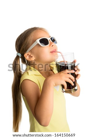 Little girl in sunglasses drinking cola beverage through a straw and looking at something above her, smiling - stock photo