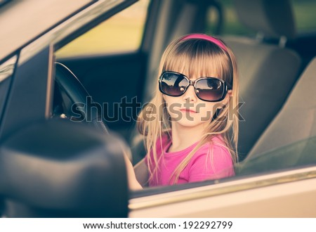 Little girl in sunglasses driving a car. - stock photo