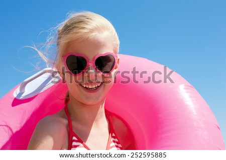 little girl in swimsuit playing with an inflatable ring on the beach. Summer vacations concept