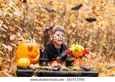 Little girl in the autumn forest of beautifully decorated table for halloween